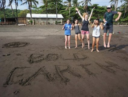 teenagers jumping on beach in costa rica