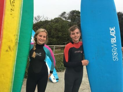 teens smiling and posing with surfboards