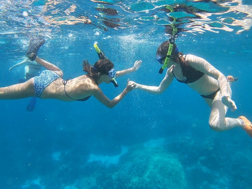 friends doing a thumb war under water while snorkeling